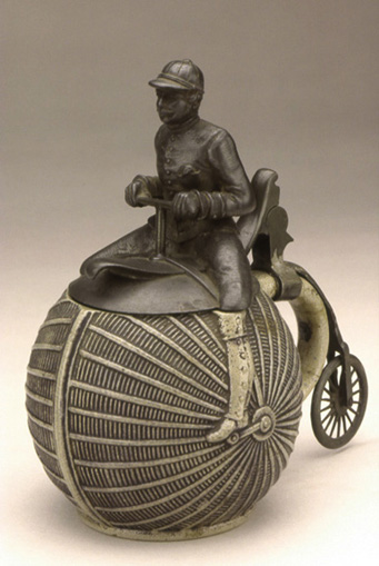 Beer Stein, ca. 1890<br> Pewter rider/lid and rear wheel<br> Stoneware container<br> Germany<br>